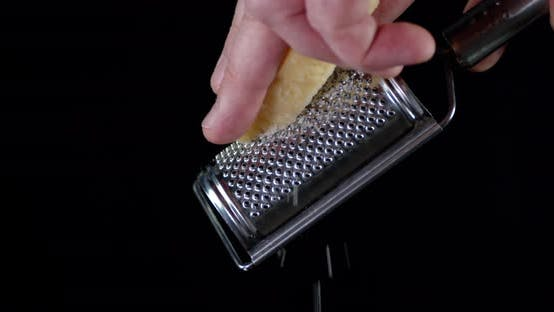 A Piece of Parmesan Cheese Shredded on a Grater.