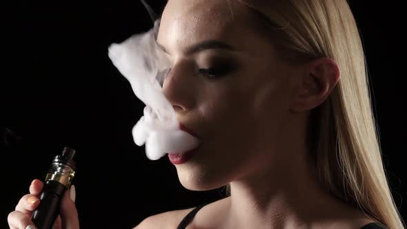 Girl Exhales Smoke and Breathes Again, Black Background. Close Up