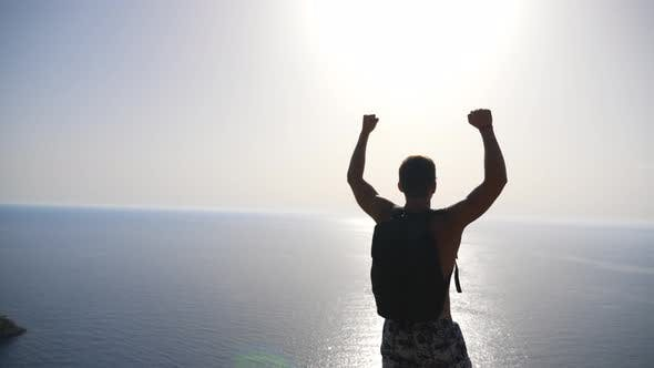 Thumbnail for Male Hiker Standing on Edge Mountain with Raising Hands and Admiring Scenic Seascape. Man with