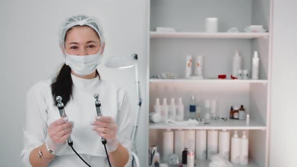 Porträt einer Kosmetikerin, die elektrische Elektroden der Mikrostromtherapie hält