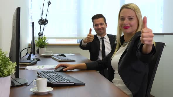 Thumbnail for Two Office Workers, Man and Woman, Work on Computers and Show Thumbs up To the Camera