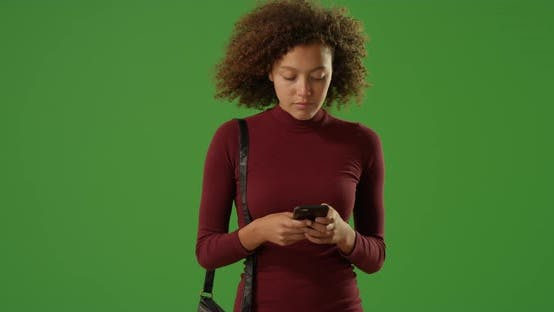 Thumbnail for Attractive African woman texting on sidewalk on green screen