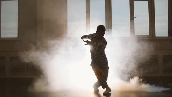 Junger Mann tanzt auf rauchigem Hintergrund