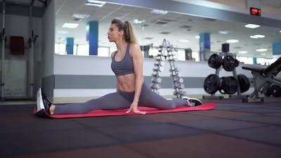 young woman stretching exercising in fitness club