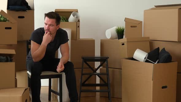 Thumbnail for A Moving Man Sits on a Chair in an Empty Apartment and Thinks About Something, Surrounded By Boxes