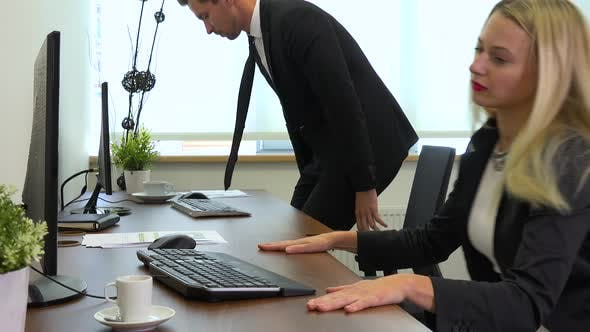 Thumbnail for Two Office Workers, Man and Woman, Sit Down to Desks with Computers and Start Working