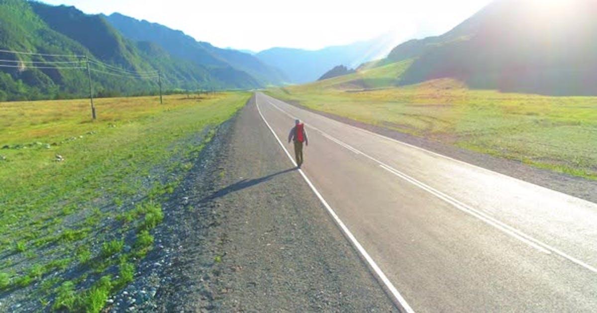 Flight Over Hitchhiker Tourist Walking on Asphalt Road. Huge Rural Valley at Summer Day. Backpack