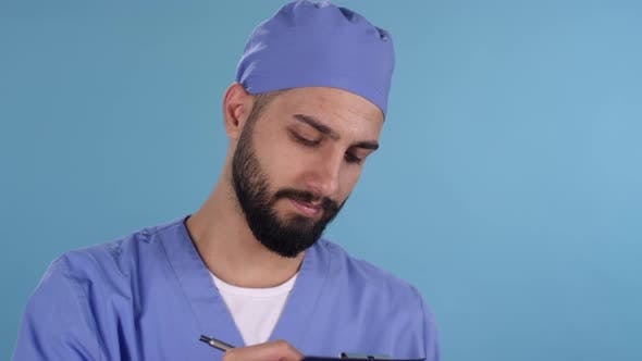 Thumbnail for Happy Male Doctor in Scrubs Smiling for Camera