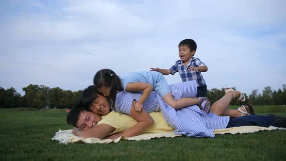 Thumbnail for Joyful Asian Family Piled on Top of Dad in Park