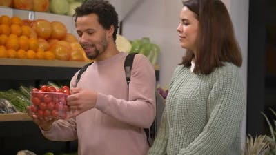 Pleased Couple Choosing Tomatoes in Supermarket