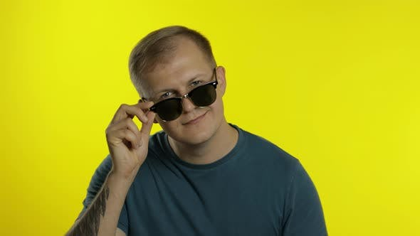 Thumbnail for Portrait of Young Man Posing in T-shirt. Cool Handsome Guy in Sunglasses Looking To Camera and Winks