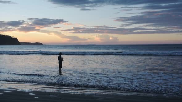 Silhouette Of A Male Photographer Capturing The Beautiful Sunset Scenery By The Sea Shore In Costa R