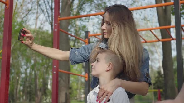 Thumbnail for Mother with Blond Long Hair Making a Photo with Her Two Young Sons in the Playground
