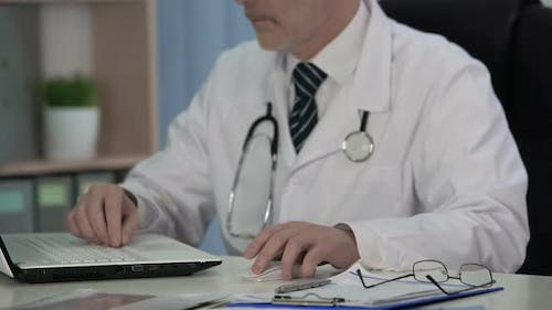 Doctor of Medical Science Writing Scientific Article for Magazine, Using Laptop