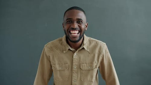 Slow Motion of Excited Guy Laughing and Having Fun Enjoying Funny Joke on Gray Background