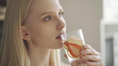 Happy Young Blonde Girl Drinks Water with Lime and Strawberry