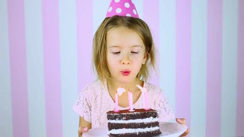 Happy and Smiling Little Girl in Pink Cap Blowing Out Candles on a Birthday Cake