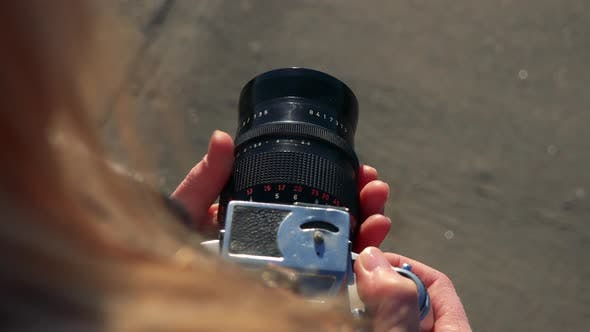 Thumbnail for A Woman Uses Zoom on a Camera - Closeup Form Above