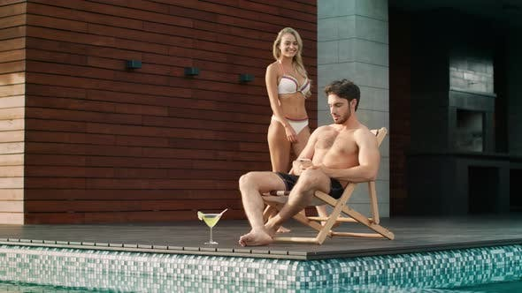 Thumbnail for Handsome Man Using Mobile Phone Near Pool at Luxury House.