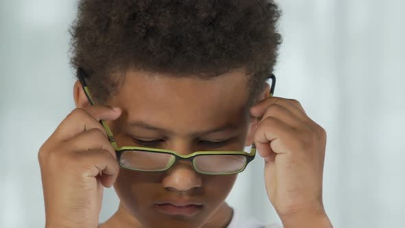 Cover Image for Little Boy Putting on Glasses Reluctantly and Taking Off, Sad Expression, Stress
