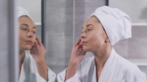 Thumbnail for Girl Touches Her Face and Looks in the Mirror