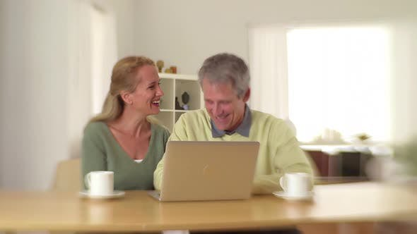Thumbnail for Senior couple sitting at desk laughing