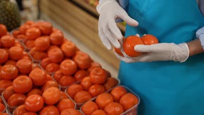Gloved Hands of Female Grocery Store Staff at Work