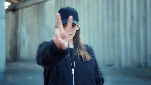 Thumbnail for Woman Showing v Sign on Urban Street. Serious Lady Showing Peace Sign Outdoors