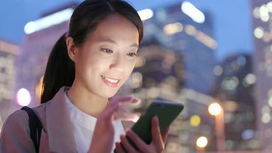 Thumbnail for Business woman use of mobile phone in city at night