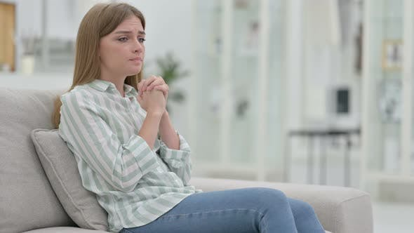 Worried Young Woman Sitting on Sofa and Thinking