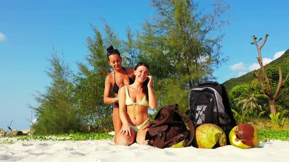 Beautiful beauty models on holiday spending quality time at the beach on paradise white sand and blu