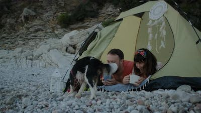 Couple drinking tea on pebble beach and  lie in tent