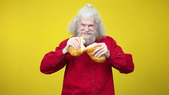 Portrait of Senior Bearded Caucasian Man Breaking Bread Loaf and Eating Tasty Crusty Bakery
