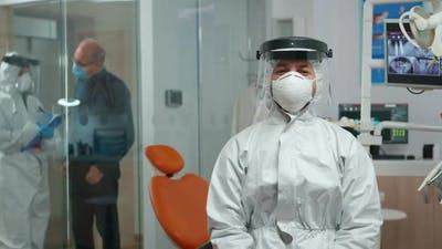 Dentist in Coverall Looking and Smiling at Camera