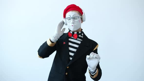 Portrait of Funny Mime Wearing Headphones Dancing Enjoying Music on White Background
