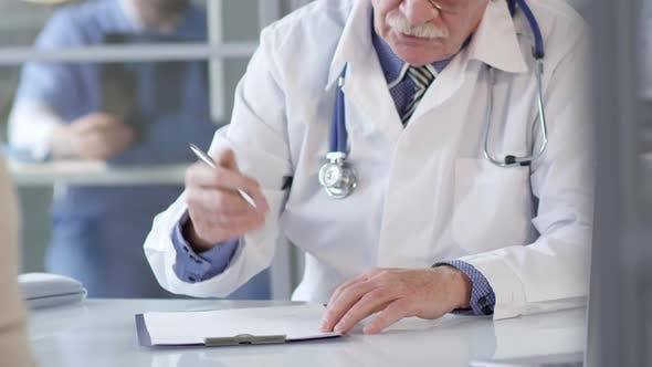 Cover Image for Senior Doctor Writing on Clipboard and Speaking with Patient