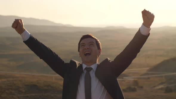 Cheerful Businessman Celebrating Victory on Nature