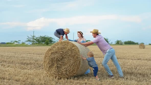 Family Fun, Parents Having Fun with Their Male Children Playing with Bale of Hay in Wheat Field