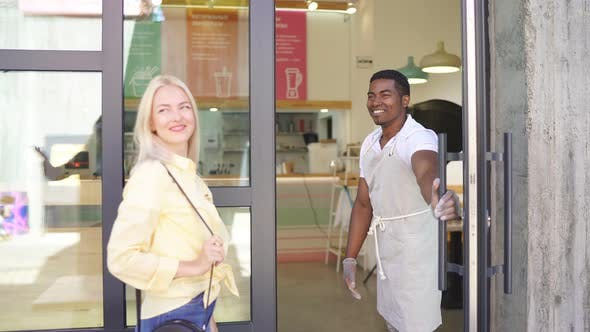 Good-looking Smiling Man Welcomes Customers.