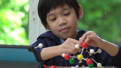 Asian Child Constructing Molecular Model  In Science Classroom