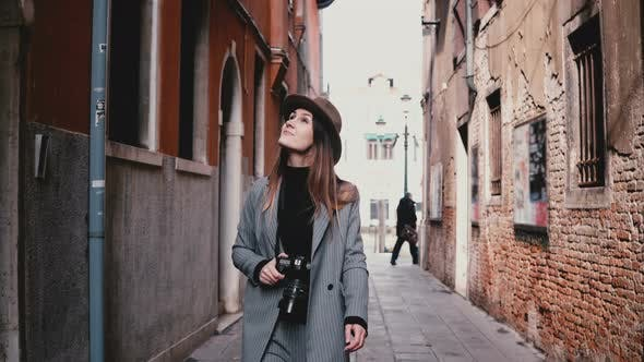 Thumbnail for Attractive Happy Professional Female Photographer Walking with Camera Smiling Along Beautiful Old