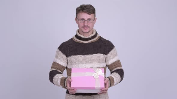 Thumbnail for Happy Handsome Bearded Man Smiling While Giving Gift Box