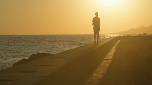 Man Walks Along the Seashore at Sunset, the Concept of Travel and Relaxation.