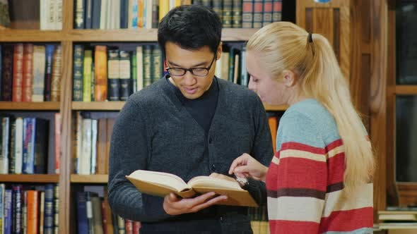 Cover Image for Asian Man with Glasses and Caucasian Women Standing Together Watching the Book in the Library.