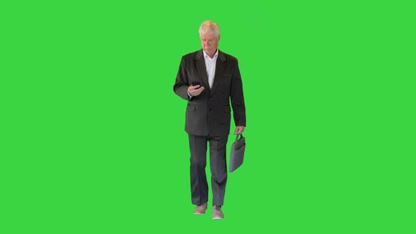 Thumbnail for Old Businessman Walking and Texting on the Phone on a Green Screen, Chroma Key.