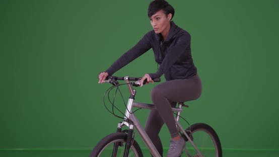 Thumbnail for Millennial black woman riding her bicycle in athletic wear on green screen