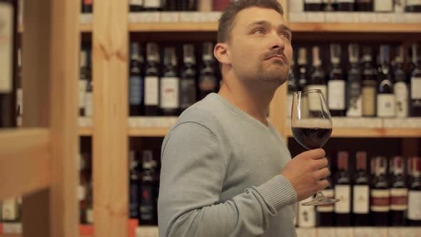 Thumbnail for Handsome Man Standing with Glass of Red Wine in Liquor Store. Woman in the Background