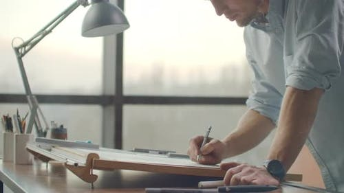 Engineer Draws Buildings on the Table Using a Pencil and Ruler