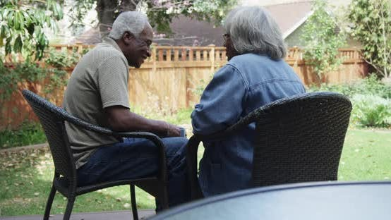 Thumbnail for Senior African couple sitting on porch drinking coffee talking