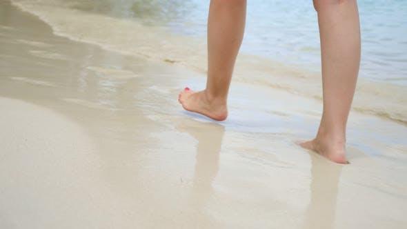 Woman Walks Along the Beach